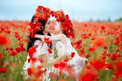 Mother and daughter playing in flower field. Beautiful mother and her daughter playing in spring flower field Royalty Free Stock Image