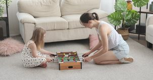 Mother and daughter playing foosball at home. Mother with her daughter having fun playing foosball at home stock video