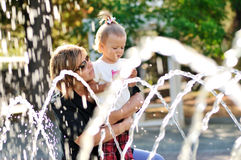 Mother and daughter playing with fountain Royalty Free Stock Photography