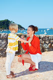 Mother and daughter playing in front of lagoon with yachts Royalty Free Stock Photography