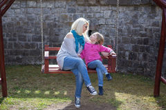 Mother and daughter playing on garden swing. Stock Photos