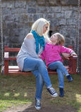 Mother and daughter playing on garden swing. Royalty Free Stock Photo