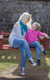 Mother and daughter playing on garden swing. Stock Photography