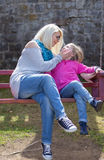 Mother and daughter playing on garden swing. Stock Photo