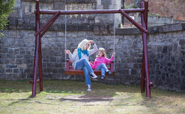 Mother and daughter playing on garden swing. Royalty Free Stock Images