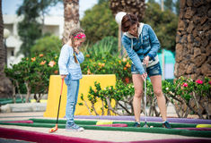 Mother and daughter playing golf Stock Image