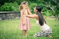 Mother and daughter playing on the grass at the day time. Stock Photos