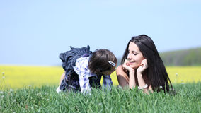 Mother and daughter playing in grass. Happy young women and girl child talking and playing in grass near yellow canola field Stock Photography