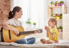 Mother and daughter playing guitar Stock Images