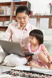 Mother and daughter playing laptop together Stock Image