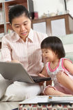 Mother and daughter playing laptop together Royalty Free Stock Image