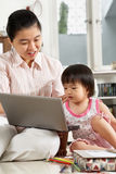 Mother and daughter playing laptop together Stock Photos