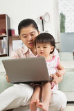 Mother and daughter playing laptop together Royalty Free Stock Images