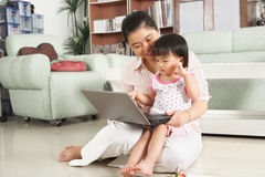 Mother and daughter playing laptop together Royalty Free Stock Photos