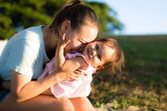 Mother and daughter playing and laughing together in park stock photography