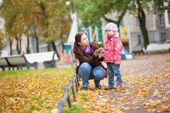 Mother and daughter playing with leaves Stock Images