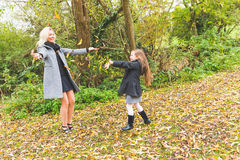 Mother and daughter playing with leaves at park in autumn Royalty Free Stock Photos
