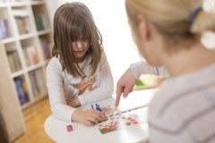 Mother and daughter playing ludo board game. Mother and daughter sitting in a playroom, playing a ludo game; daughter repositioning the pawn Royalty Free Stock Image