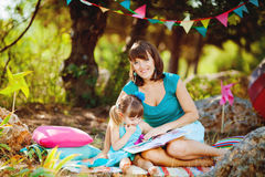 Mother and daughter playing outdoors in summer Stock Photos