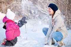 Mother and daughter playing outdoors at winter Royalty Free Stock Image