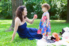 Mother and daughter playing in park Stock Photography