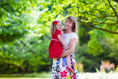 Mother and daughter playing in a park Stock Photos