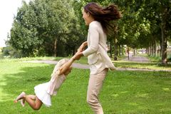 Mother and daughter playing at the park. Portrait of happy mother and daughter playing circling around at the park stock images