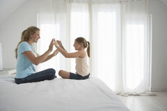 Mother And Daughter Playing Patty-Cake On Bed Stock Image