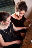 Mother and daughter playing piano Stock Photos