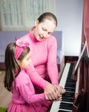 Mother And Daughter Playing Piano Stock Image
