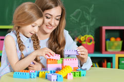 Mother and daughter playing with plastic blocks Royalty Free Stock Photography