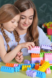Mother and daughter playing with plastic blocks Stock Photos