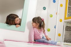 Hide and seek. Mother and daughter playing in a playroom, hiding in a small wooden house, playing hide and seek Royalty Free Stock Photos