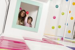 Mother and daughter throwing balls. Mother and daughter playing in a playroom, hiding in a small wooden house, throwing balls through the window stock image