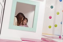 Whispering and storytelling. Mother and daughter playing in a playroom, hiding in a small wooden house, whispering and storytelling Royalty Free Stock Photo