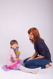 Mother and daughter are playing with a plush toy Stock Image