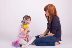 Mother and daughter are playing with a plush toy Royalty Free Stock Images