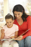Mother And Daughter Playing Reading Book At Home Royalty Free Stock Photos