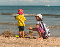 Mother and daughter playing with sand on the beach Stock Photography