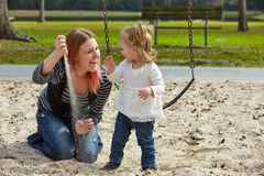 Mother and daughter playing with sand in park Stock Photos