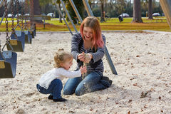 Mother and daughter playing with sand in park Stock Photo