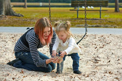 Mother and daughter playing with sand in park Royalty Free Stock Photos