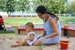 Mother and daughter playing in a sandbox Stock Images