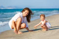 Mother and daughter playing on the sea beach in Greece royalty free stock photo