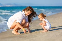Mother and daughter playing on the sea beach in Greece royalty free stock images