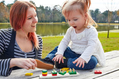 Mother and daughter playing with shapes in park Royalty Free Stock Photos