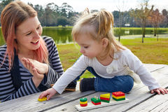 Mother and daughter playing with shapes in park Royalty Free Stock Image