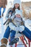 Mother and daughter playing with sled Royalty Free Stock Image