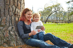 Mother and daughter playing with smartphone Royalty Free Stock Images