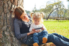 Mother and daughter playing with smartphone Stock Images